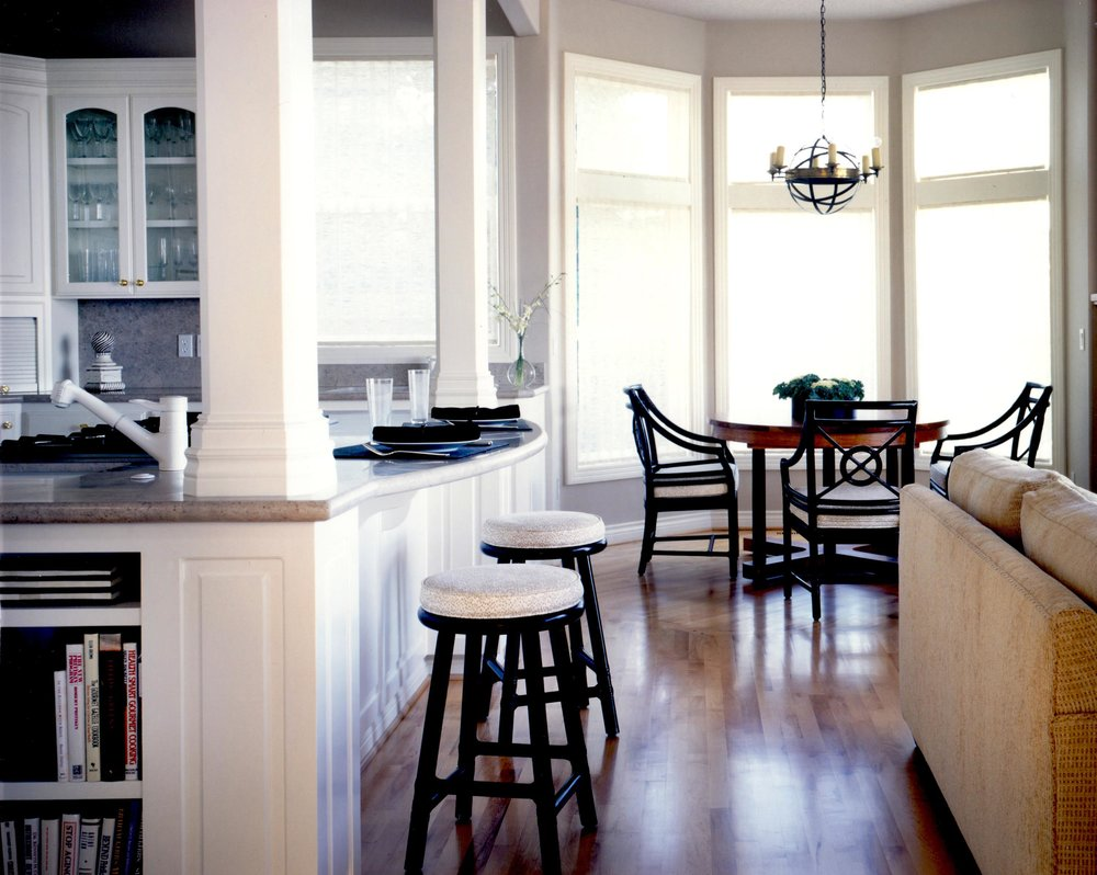 House interior with hardwood floor, bar stool, round table and chairs