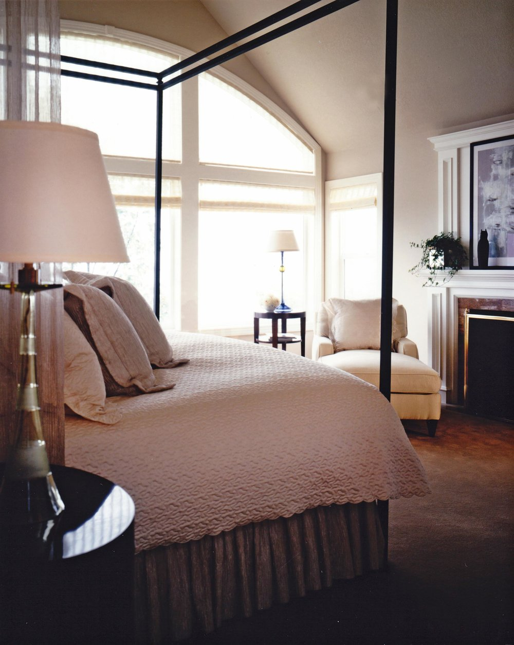 Bedroom interior with large window, table lamps, armchair and fireplace