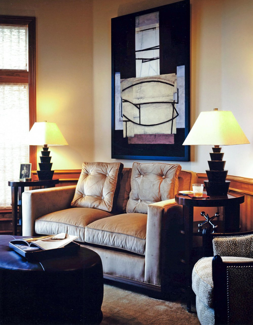 Living room with sofa, round side table each side of sofa, table lamp and artwork on wall