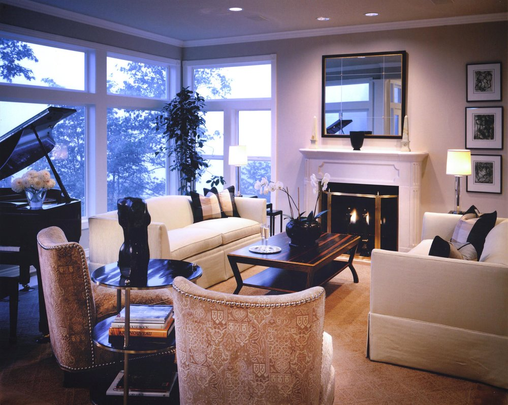 Living room with sofa, wooden center table, large window, fireplace and piano on the side