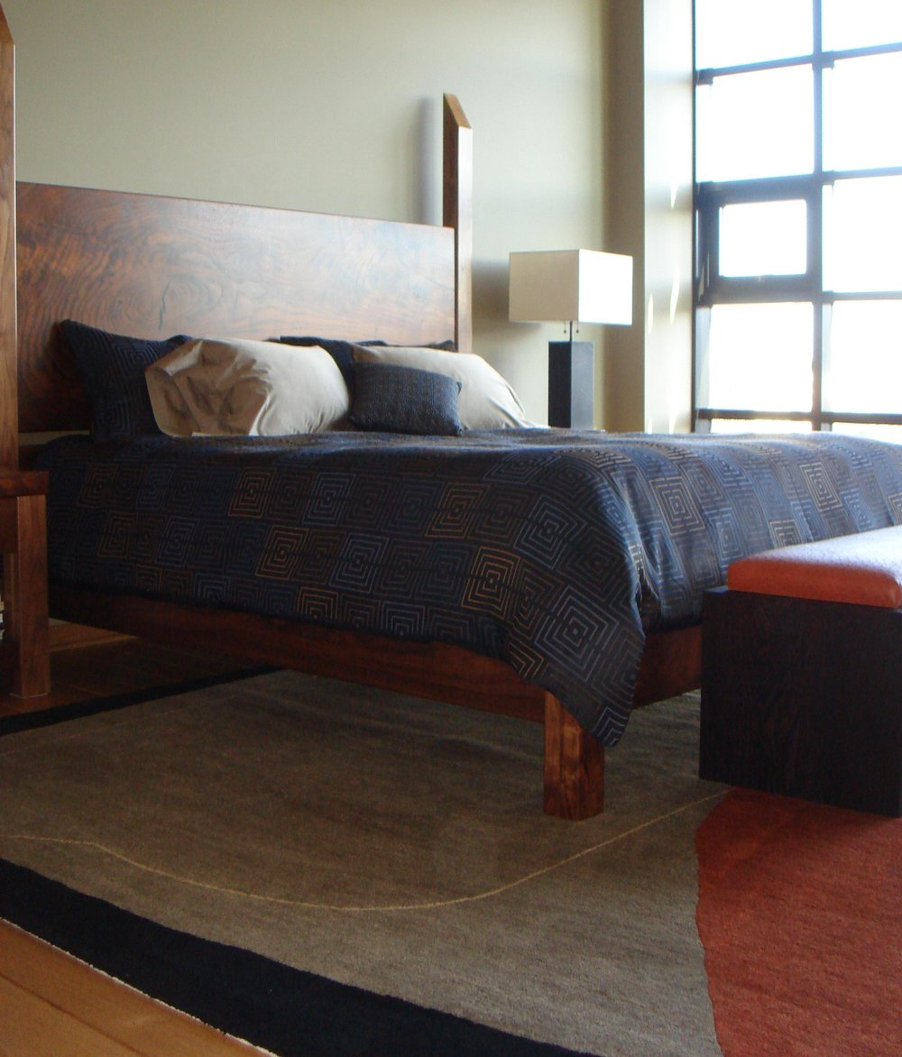 Large wooden bed with mattress, carpet and table lamp