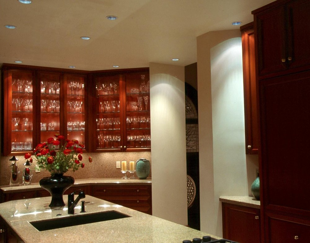 House bar with granite countertop, wine glasses in a wooden cabinet