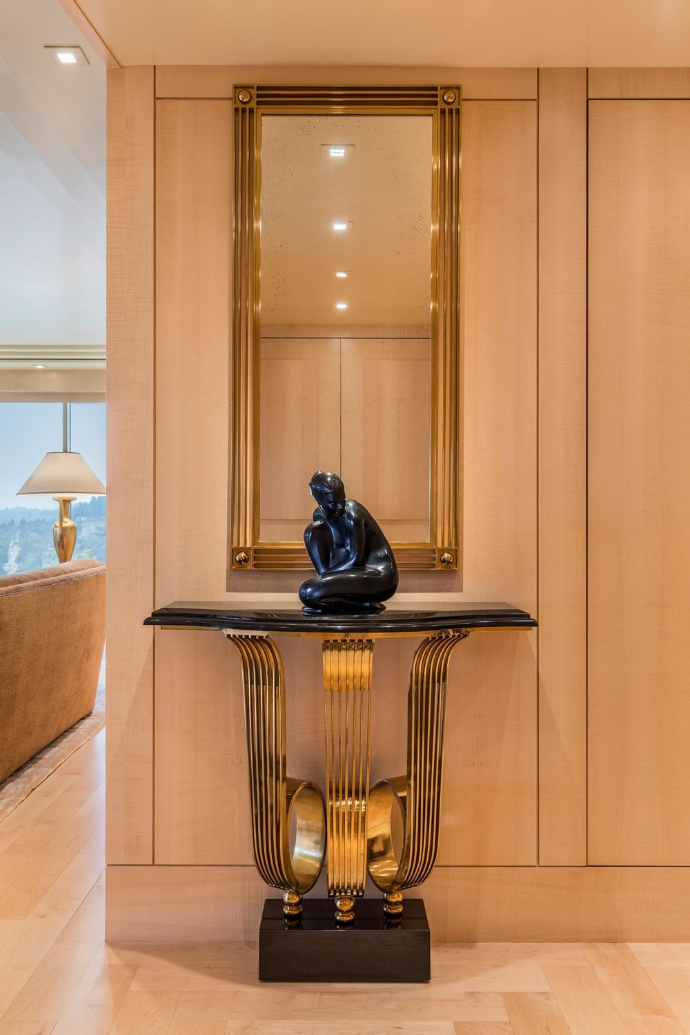 A table with statue on top, and a rectangular mirror on wall