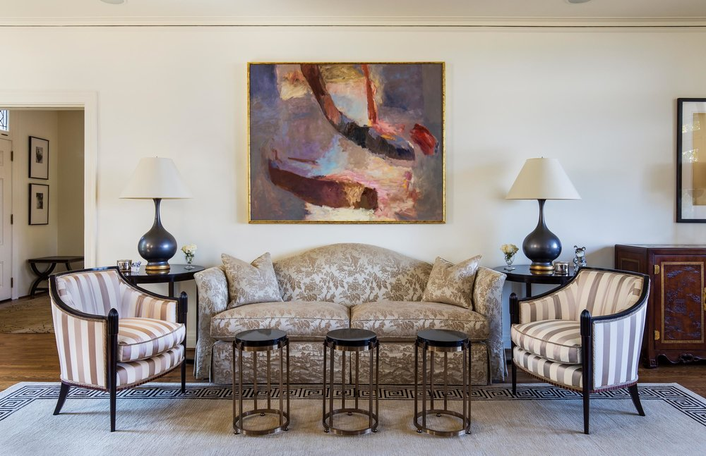 Modern living room with sofa, large carpet, table lamps and artwork