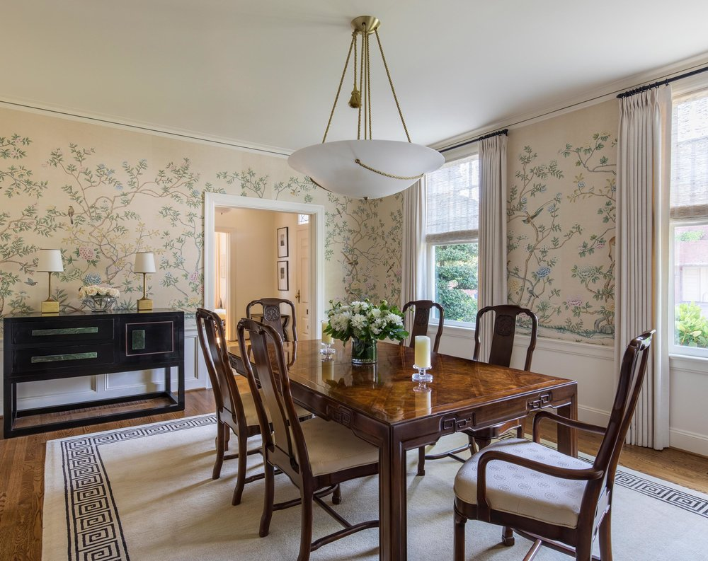 Dining room in a printed wall with wooden table and chairs and a large carpet