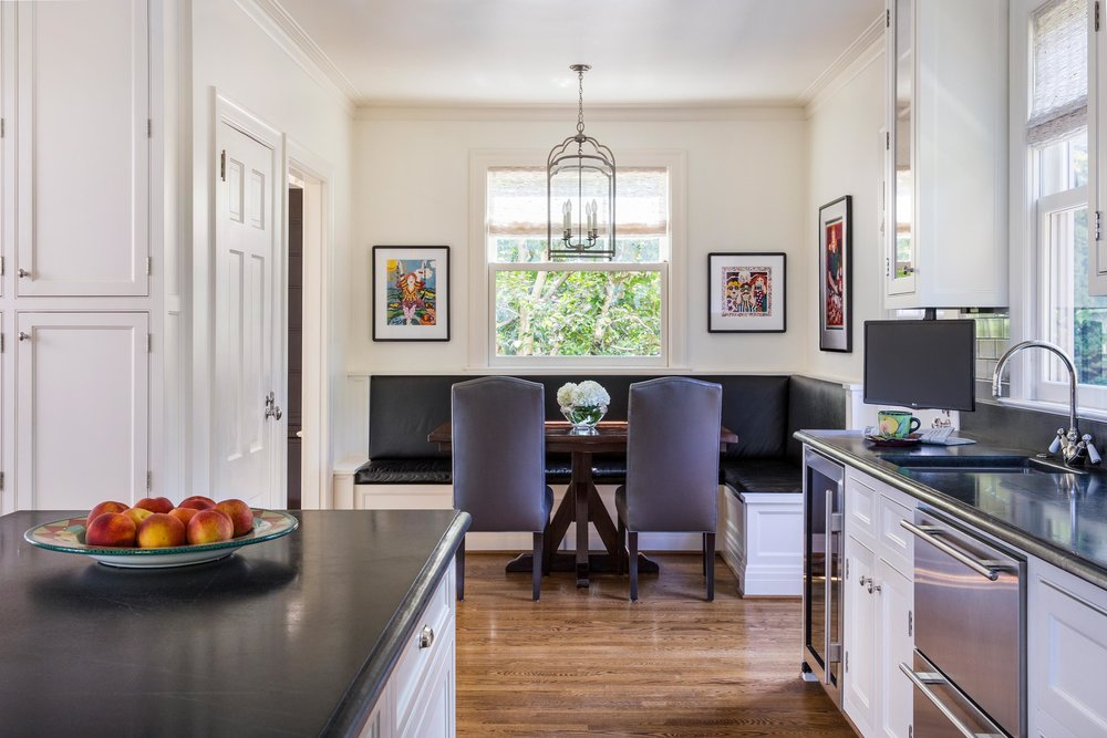Dining room interior with white wall, hardwood floor and wooden center island