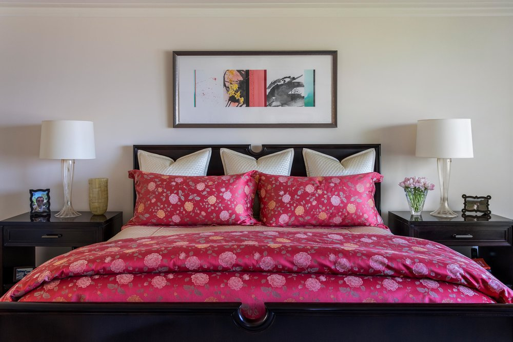 Bedroom with large bed, a frame, bedside table and lamp on top