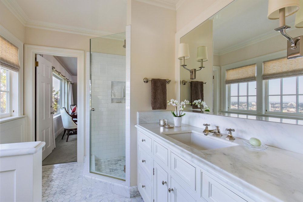 Bathroom with granite counter top, white cabinet and  large mirror on wall