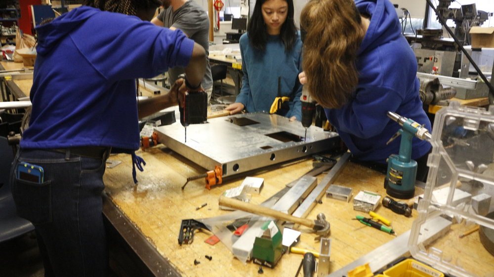 - All girl robot frame assembly crew.