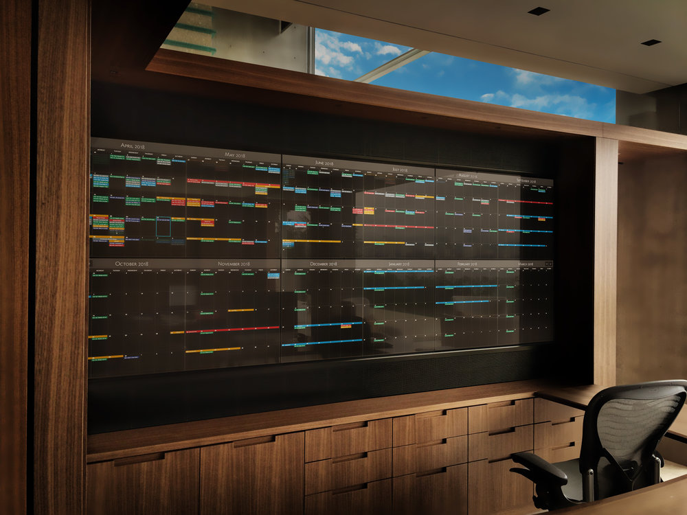 A custom six-screen video wall covered in touch sensitive glass, features a very powerful, custom developed calendar application for this homeowner's stunning office. They needed a way to better visualize a full year of their dymanic calendar to help discover opportunities for more time for adventure.