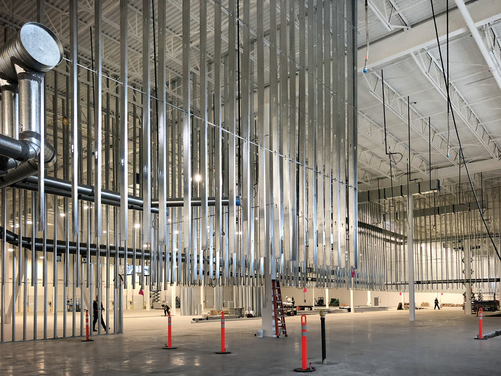 Hundreds of steel studs that will form 34-foot walls hang from the ceiling before being extended to the floor.