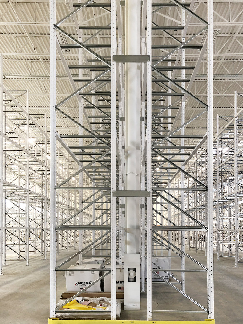 Beautiful, gleaming and white, the pallet the merchandise shelving is a geometric site to behold. It's also a major obstacle to accessing the ceilings, so it was staggered with the other installs to avoid conflict.