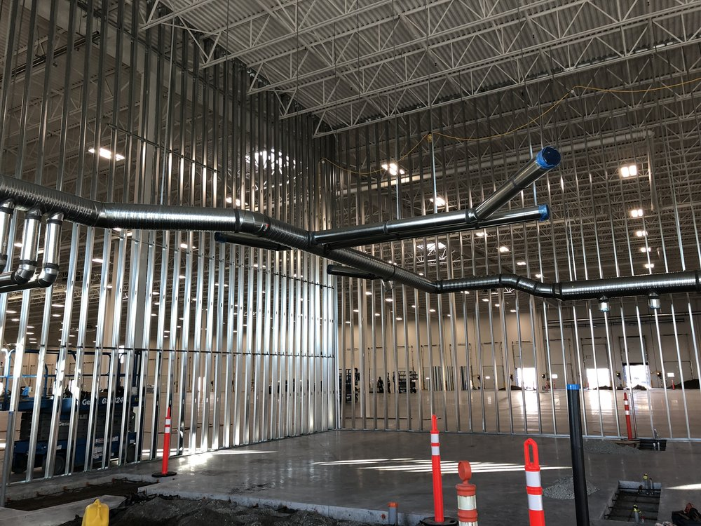 Steel studs extending from ceiling to floor, awaiting cabling and board. Concrete trenching is seen in the foreground for services being added in what will be an office floor.