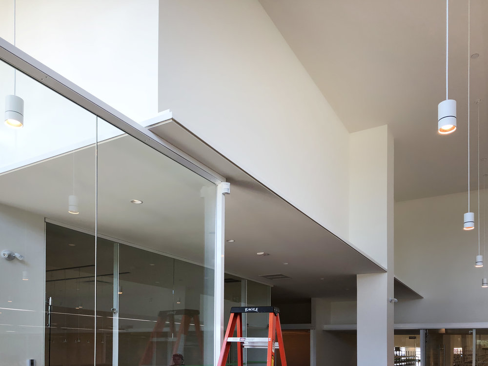 Many motion sensors are located above doorways throughout the space, mounted high on walls to minimize their visibility.
