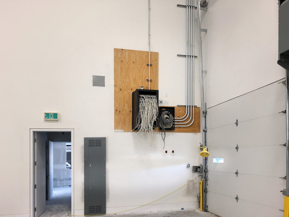 This equipment cabinet has its network cabling fed into it, and is ready to be trimmed, terminated and punched down into the patch panel. To its right, a security system enclosure has cables looms sitting in it ready for a similar process.