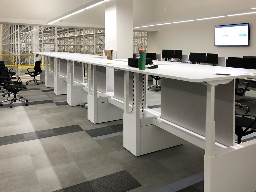 Beautiful sit-stand desks being installed in many of the workstation pods in the offices at the facility.
