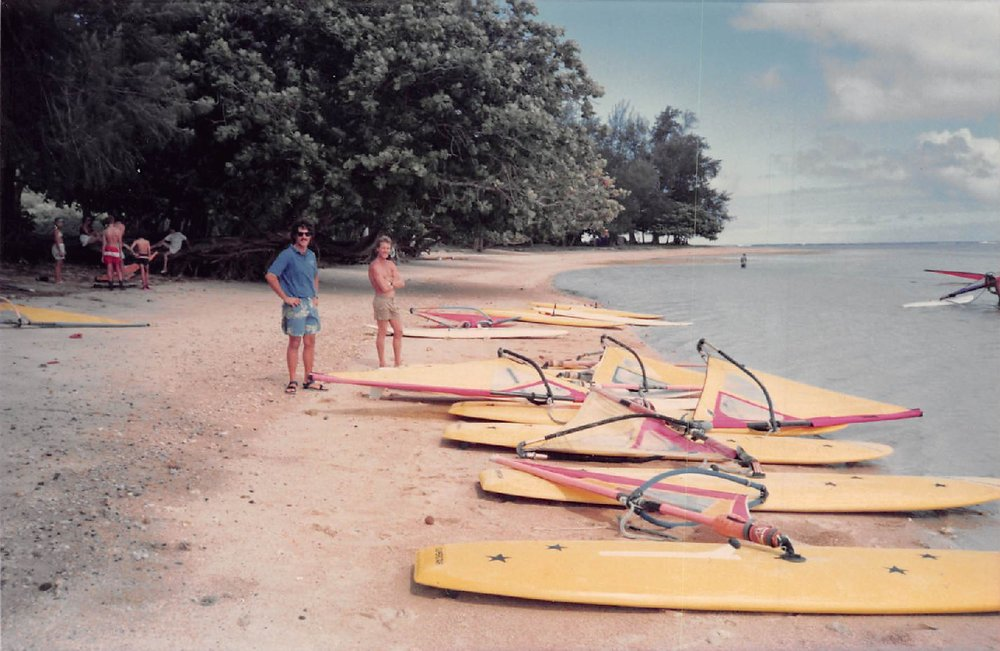 - Pierre encouraged me to buy an extra rig as he was sure someone would want it. The rig was sold before it even got to Kauai. Soon the extra bedroom in my Princeville house was full of new equipment for sale. Jimmy Lewis, a new friend and shaper I had met, was in my garage shaping the world's greatest sailboards under the Cowden Hawaii label. Windsurfing equipment was improving on a weekly basis and cars were lining up the street. We pioneered new windsurfing spots all over Kauai. Every morning we listened to George Mason's weather report on KGU radio and consequently became quite astute at forecasting the wind and waves. It was an exciting time.Photo: Hanalei Sailboard's windsurfing instructors Foster Ducker and Keith Morrison | Anini Beach | Circa 1988