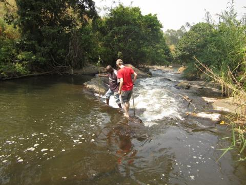 In Uganda, University of New Hampshire undergraduate student Michael Casazza crosses a river with local help to access a forest on the edge of Kibale National Park. Soils from the forest and nearby agricultural fields are being compared in a study of the socioeconomic factors driving agricultural sustainability in a region with one of the planet's highest rates of population growth.