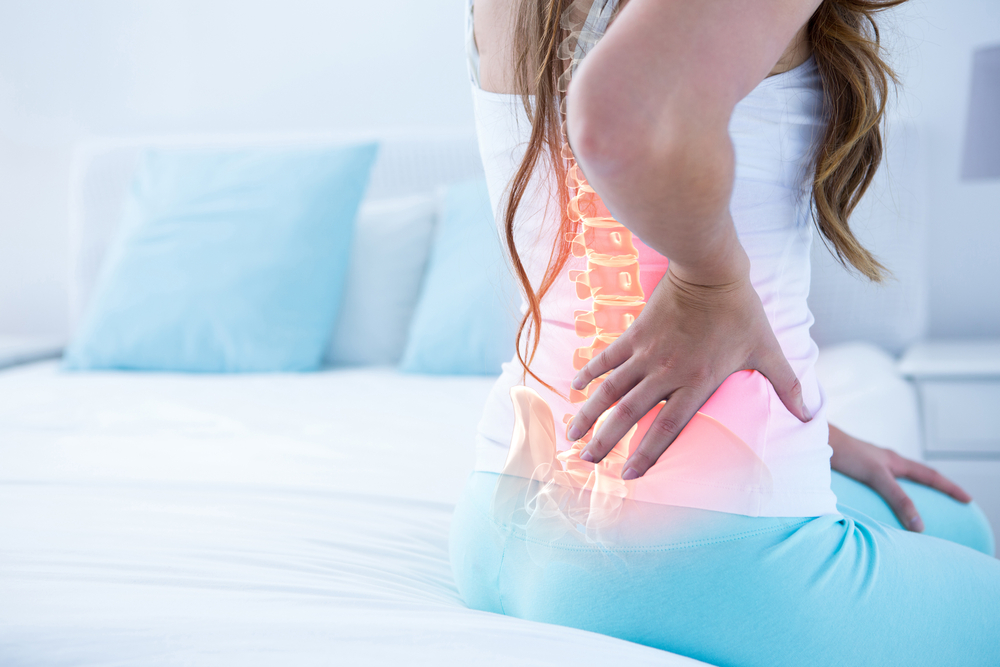 Digital composite of highlighted spine of woman with back pain at home.jpg