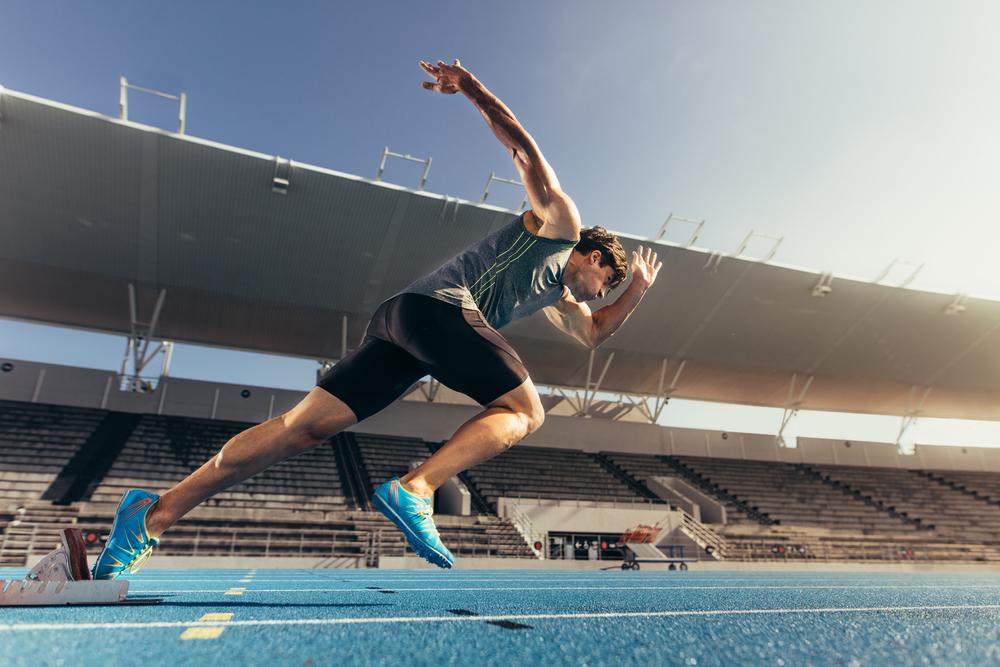 Athlete using starting block to start his run on running track in a stadium.jpg