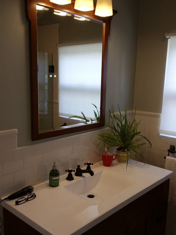 New vanity, light & mirror accented with a tile wainscotting.