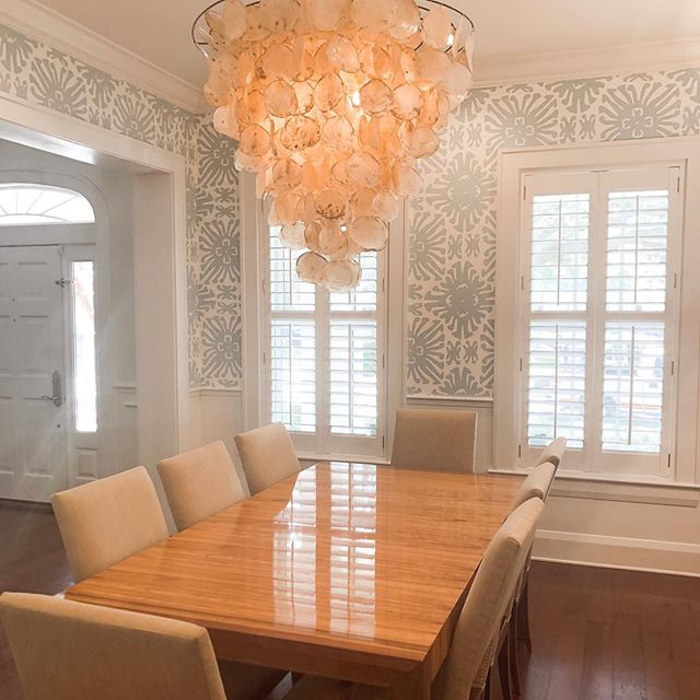 """Who is on board with wallpaper like we are?! Some say it is """"coming back,"""" but we don't think it ever left.  Check out todays blog (link in bio ☝🏻) for some of our pro tips and favorite vendors when it comes to covering those walls of yours💥. Pic taken from our dear client's dining room where we installed @quadrillefabrics wall covering🥰 . . . . #wallpaper #wallpaperdecor #walldecor #diningroom #diningroomdecor #diningroomideas #lighting #chandelier #verytandc #bhghome #coastal_living #floridadesign #floridadesigner #southfloridaliving #aliciaweaverdesign #olystudio #quadrillefabrics"""