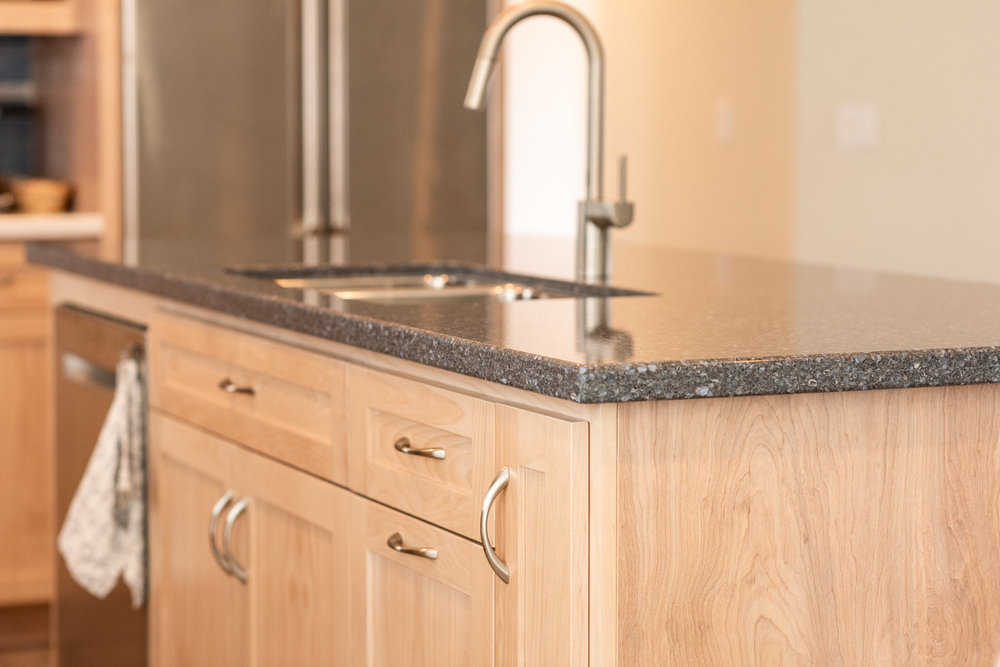 Coastal Contemporary custom kitchen cabinets with natural wood stain and corian counter tops