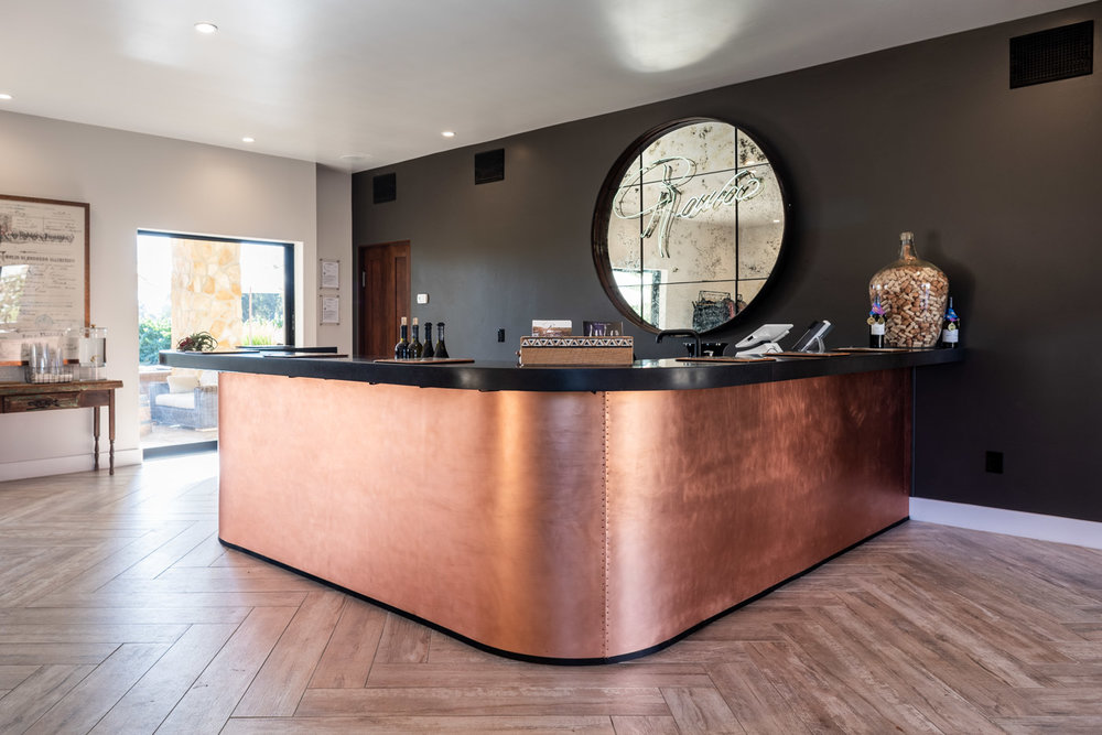 Industrial tasting room bar with custom cabinets and concrete countertop