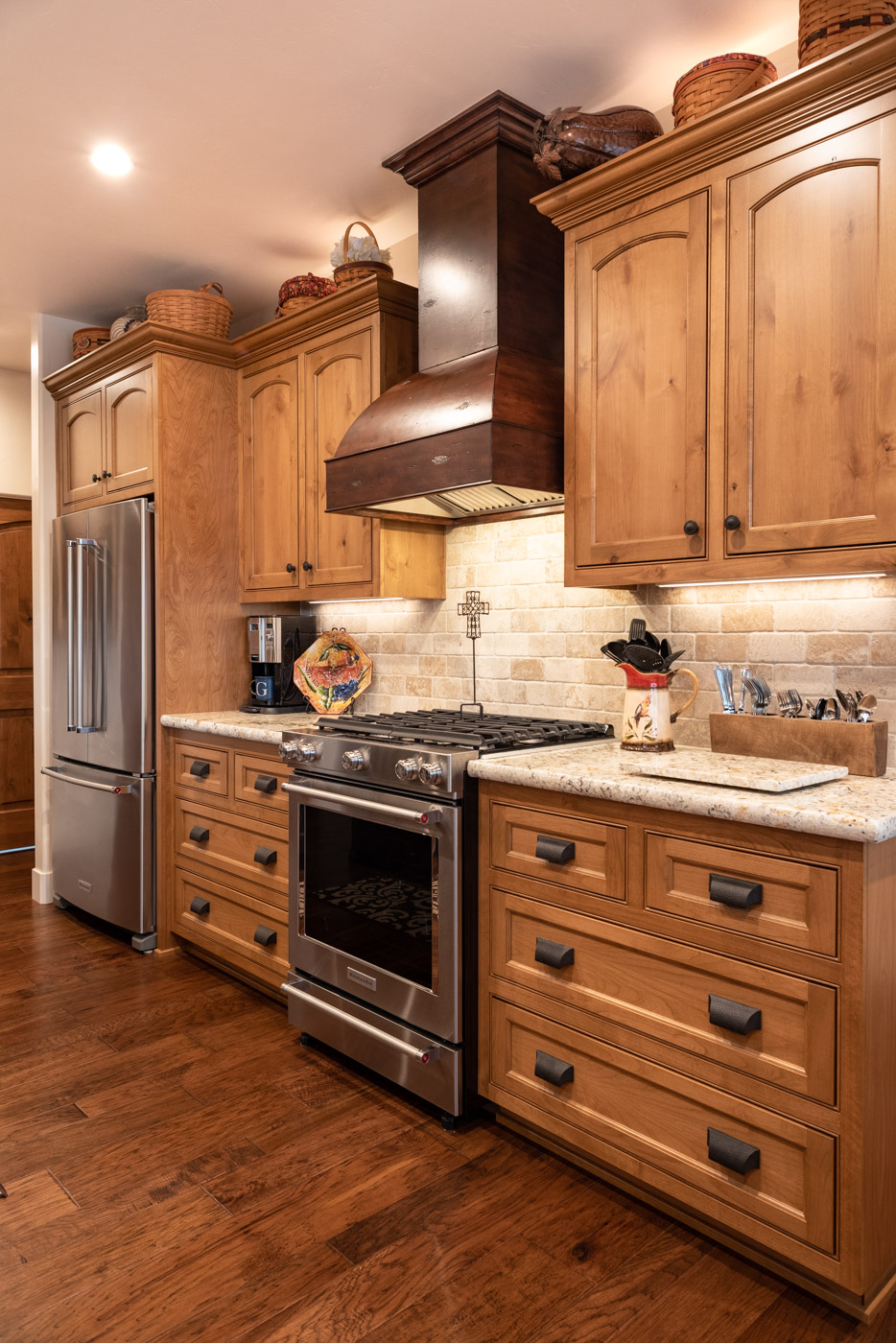 Tuscan Artisan custom stained Alder wood kitchen cabinets and range hood