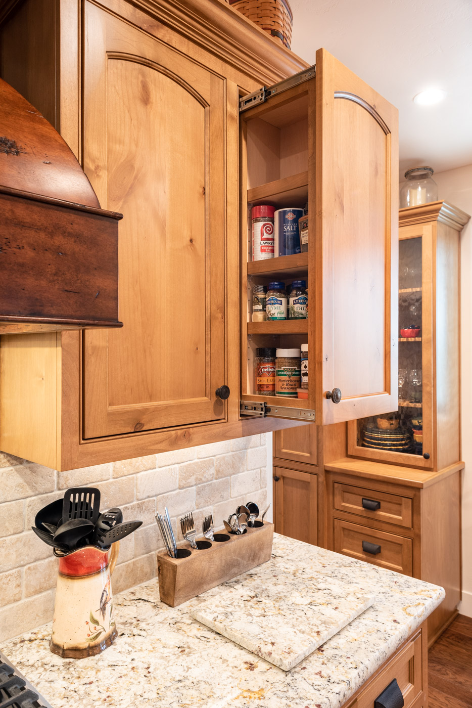 Tuscan Artisan custom stained Alder wood kitchen cabinet spice storage