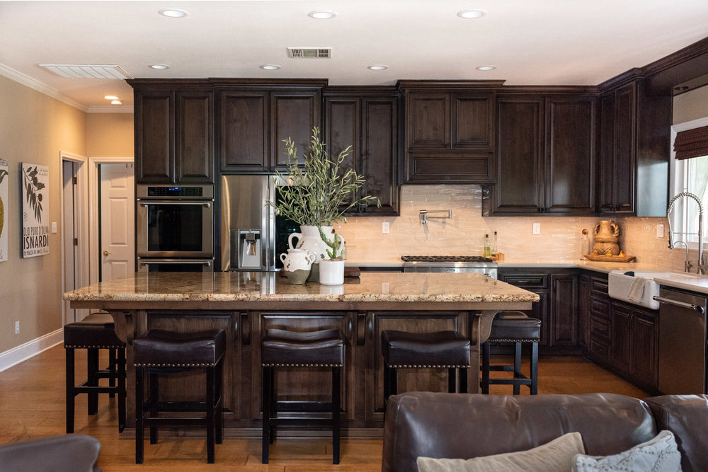 Traditional Mediterranean kitchen with dark wood stain cabinets and large island