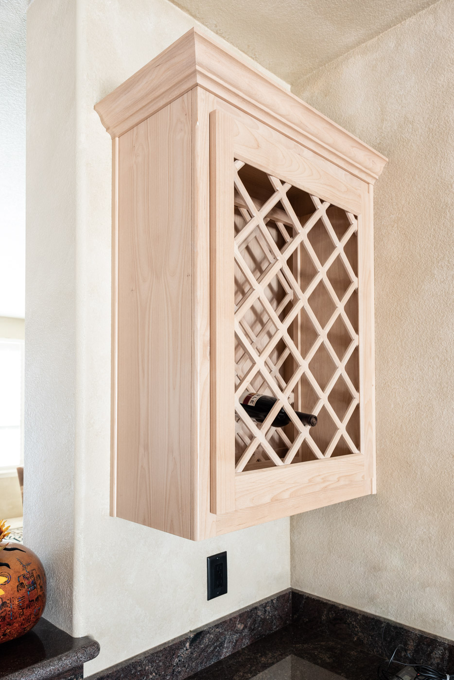 Simple Southwestern custom kitchen cabinets in white washed wood stain with custom wine rack storage