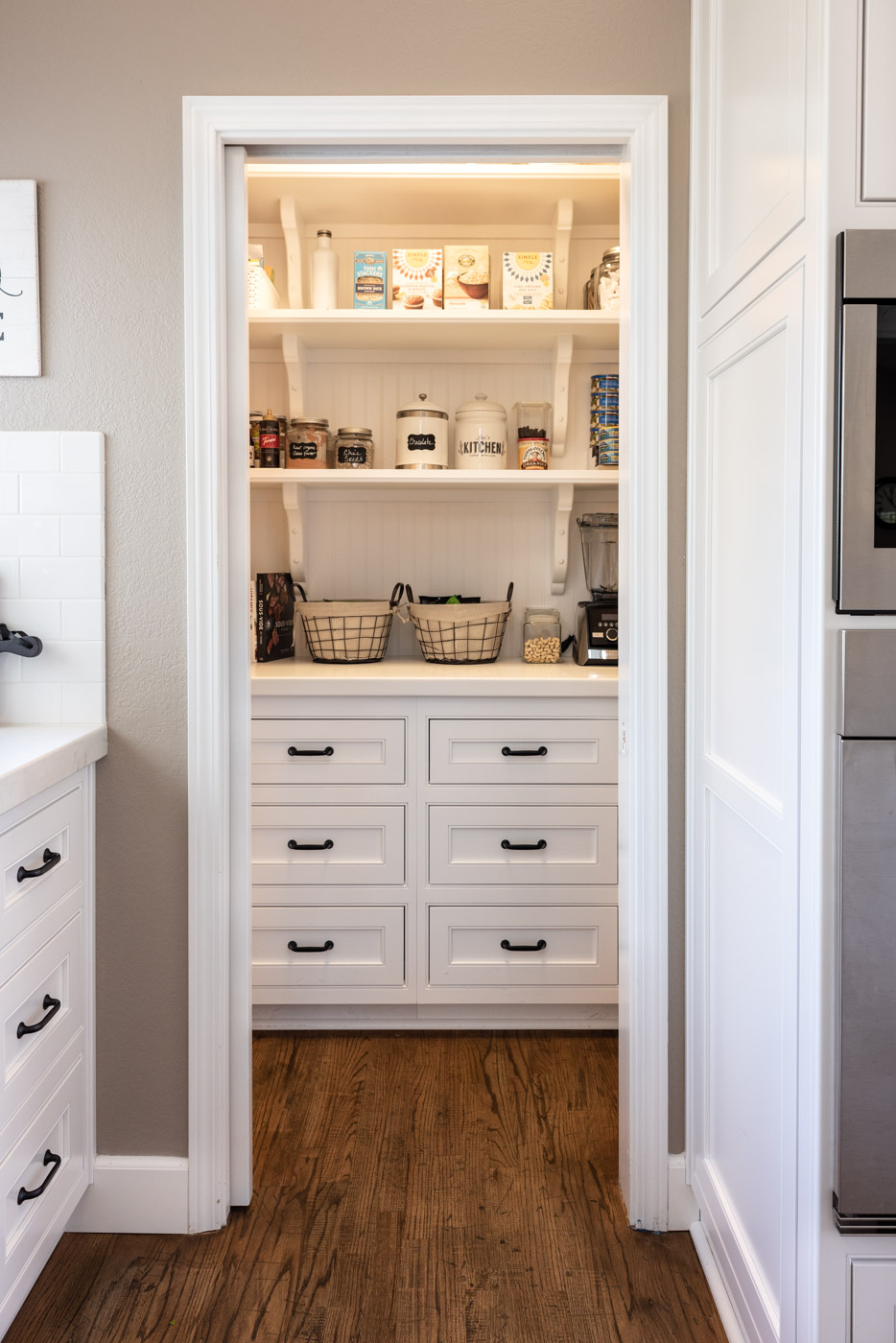 Transitional Country Cottage style kitchen with white painted cabinets and custom pantry storage