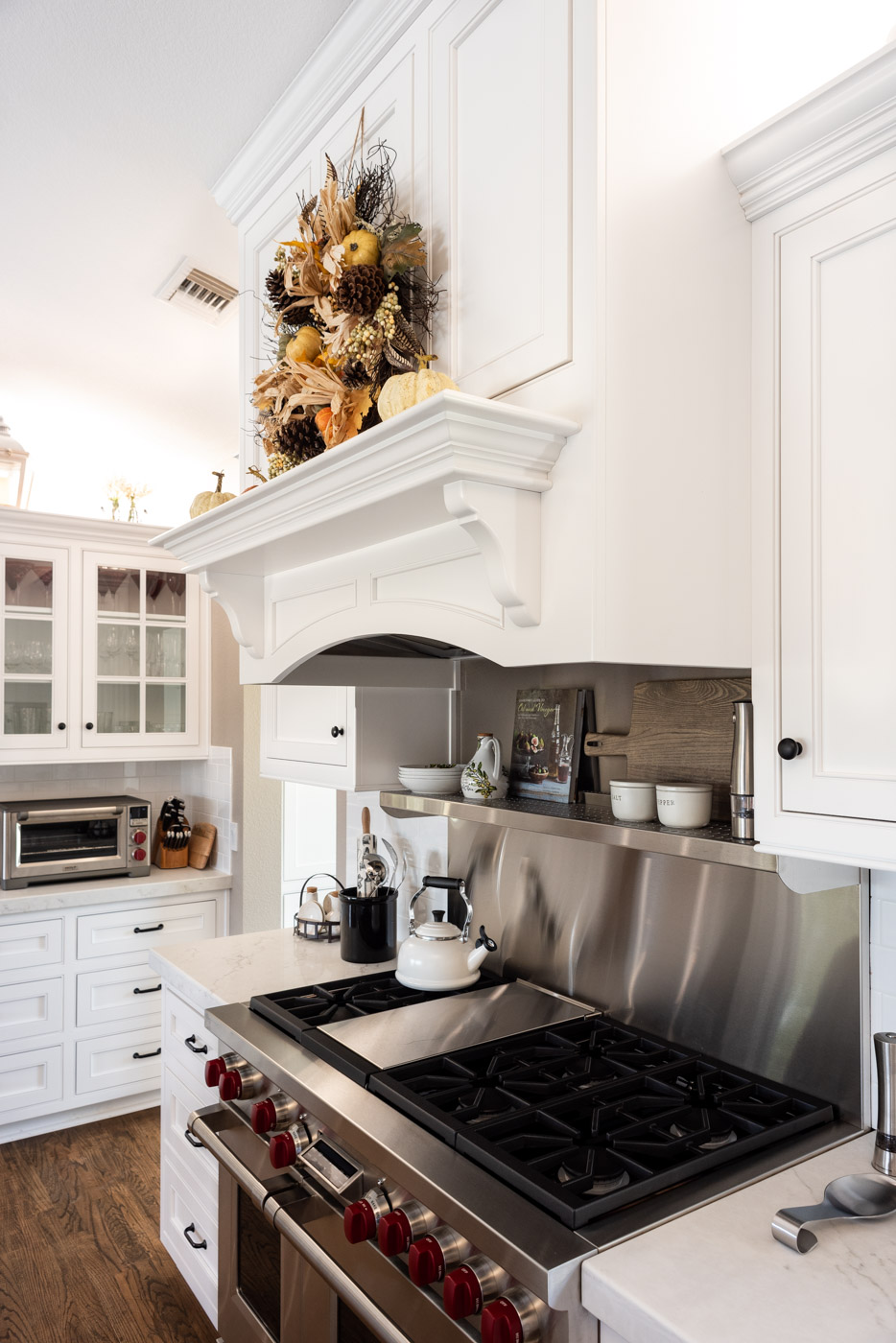 Transitional Country Cottage style kitchen with white recessed panel painted cabinets and custom range hood