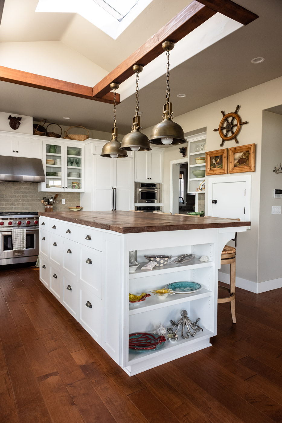 Coastal Craftsman kitchen with custom white painted shaker cabinets and island storage