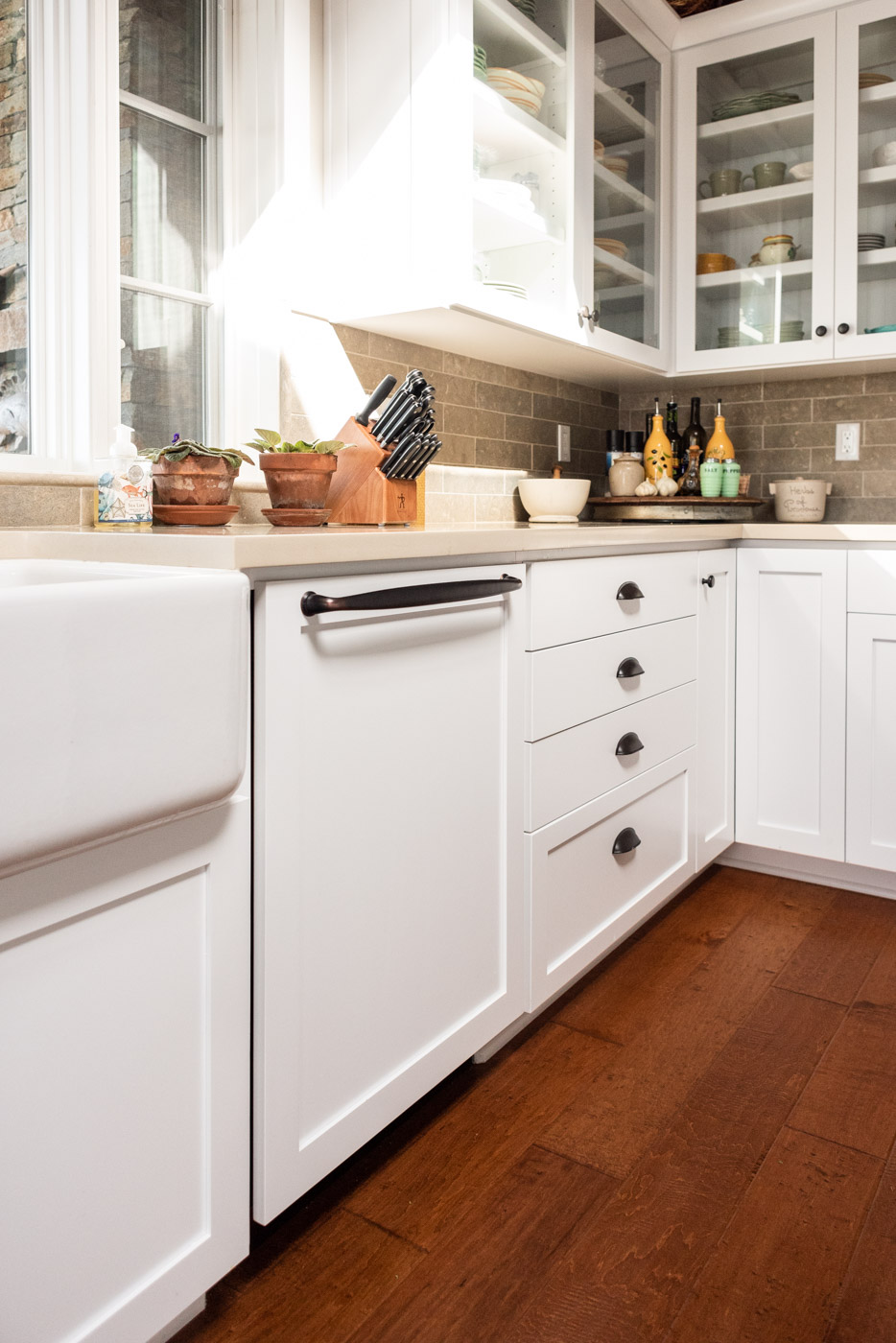 Coastal Craftsman kitchen with custom white painted shaker cabinets and dishwasher panel