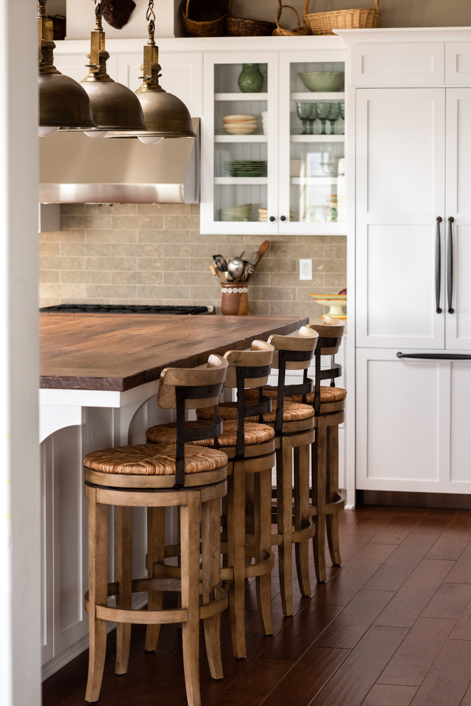 Coastal Craftsman kitchen with custom white painted shaker cabinets and island bar seating