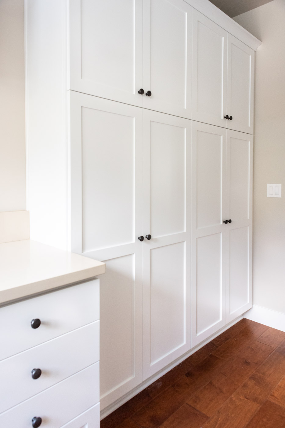 Coastal Craftsman home with custom white painted laundry room linen closet cabinets