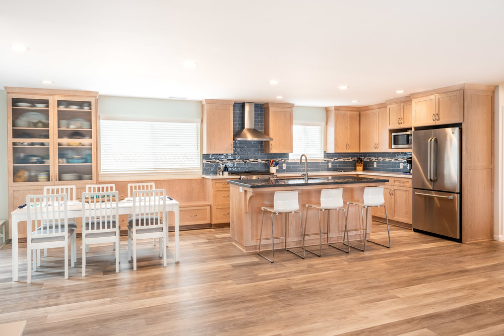 An L-shaped kitchen layout with custom cabinets in a natural wood finish