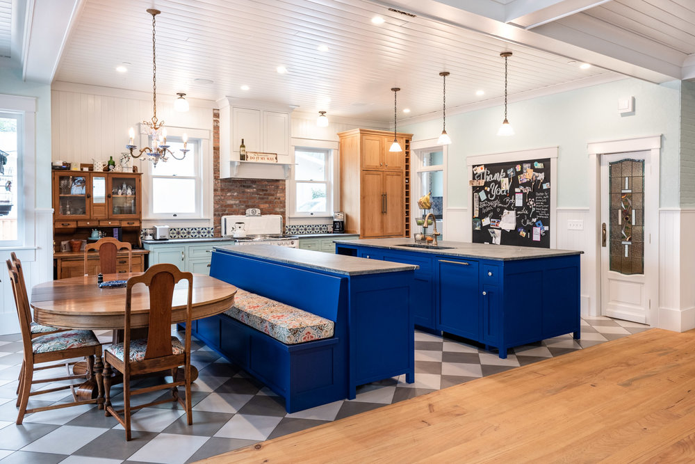 An expansive kitchen/dining area with a U-shaped layout using multiple kitchen islands