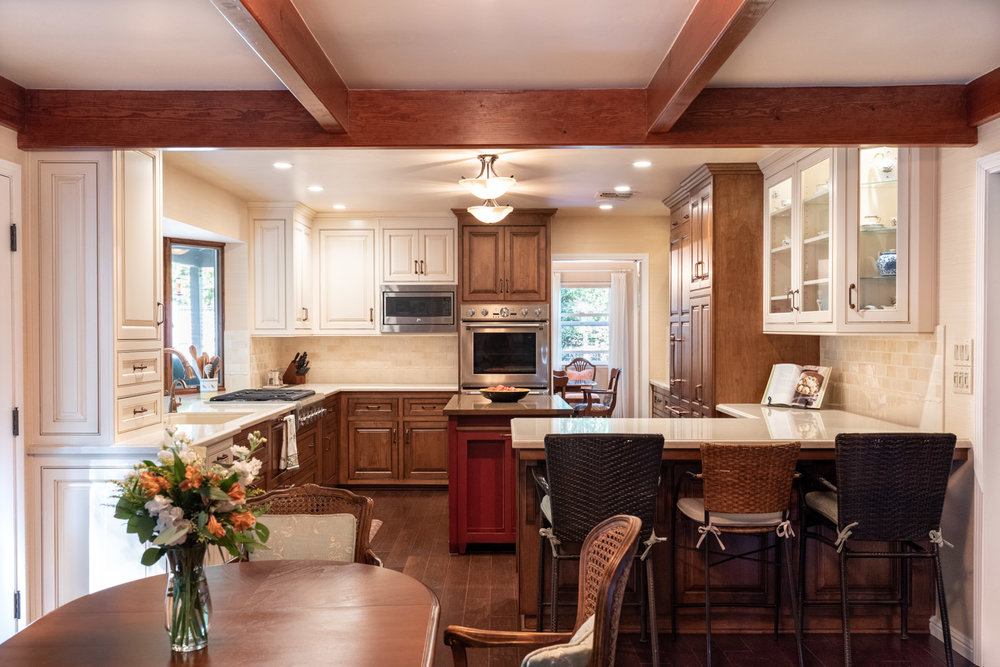A G-shaped kitchen layout with custom cabinets in mixed finishes, including white painted cabinets and wood stained cabinets