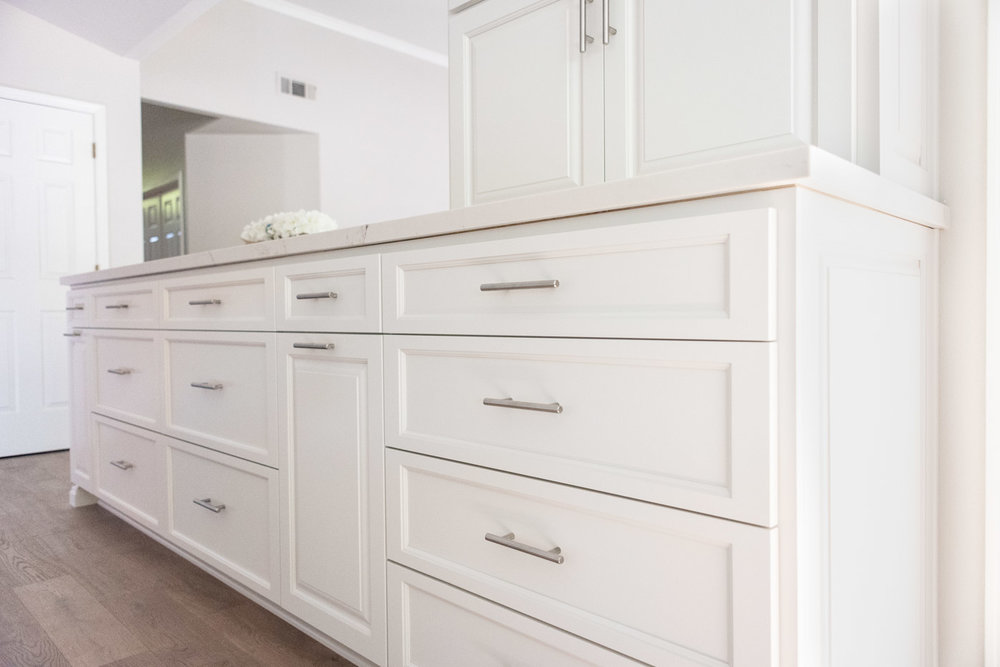 Contemporary brushed nickel bar pulls against custom white painted recessed panel cabinet drawers and doors
