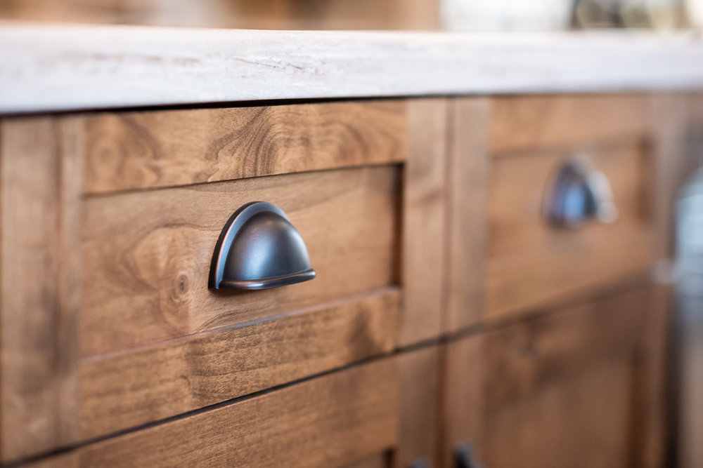Cabinet drawer cup pulls in an antique bronze finish against a medium stained Knotty Alder wood cabinet