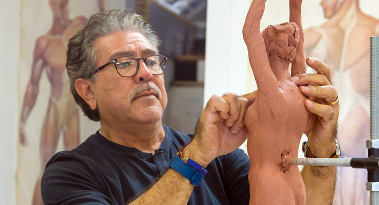 Teale Street student Dan Romero refines his sculpture of a yogini in tree pose. Photos by Inae Bloom