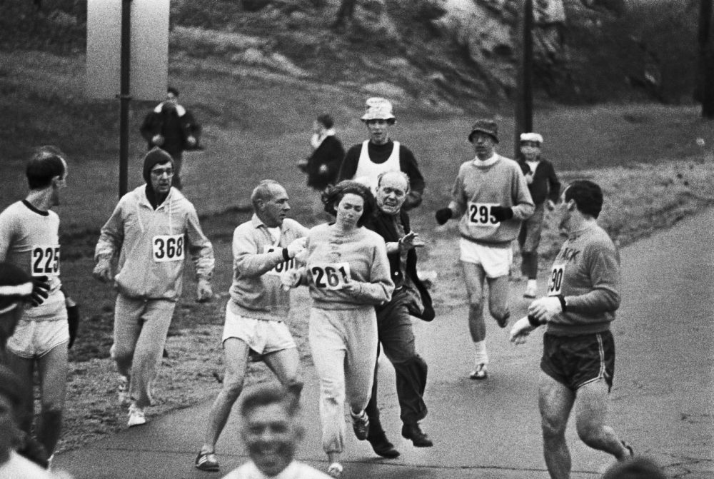 An official trying to physically remove Kathrine Switzer from the Boston Marathon, two miles in, in 1967. Cred: Wbur