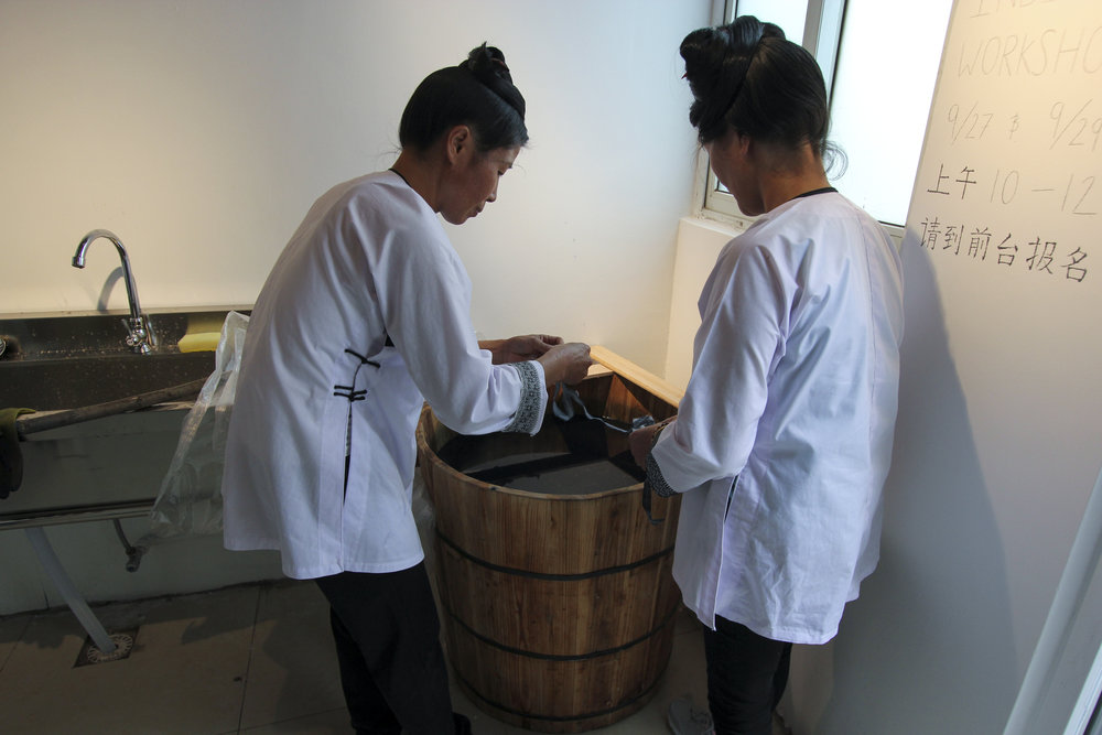 Shenshu and Bimeng help tend to the dye bath—that needs continued attention.