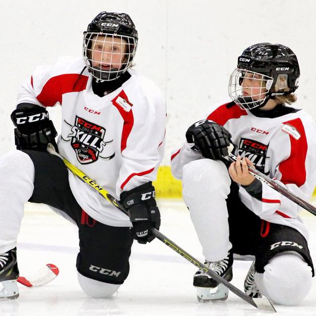 Two junior ice hockey players kneeling