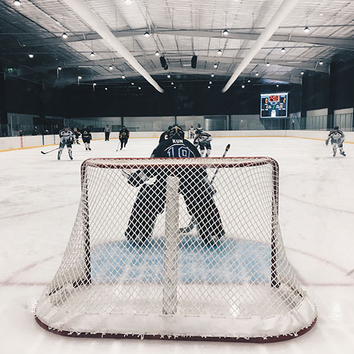 rear view of ice hockey goalie in goal crease with iceHQ beer league players skating towards him