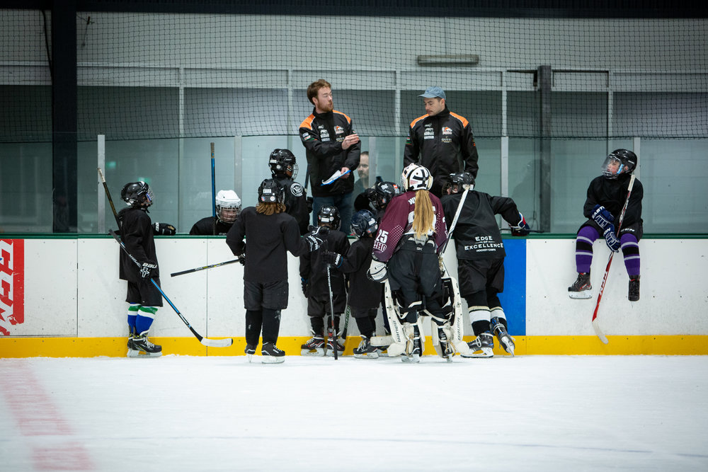 class of junior ice hockey students receiving coaching instructions