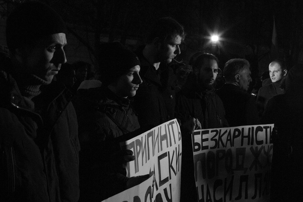 """The activists with posters in the shadow: """"Stop raids by masked police"""", """"the impunity generates violence"""". And lighten person is the leader of the right-wing organisation C14."""